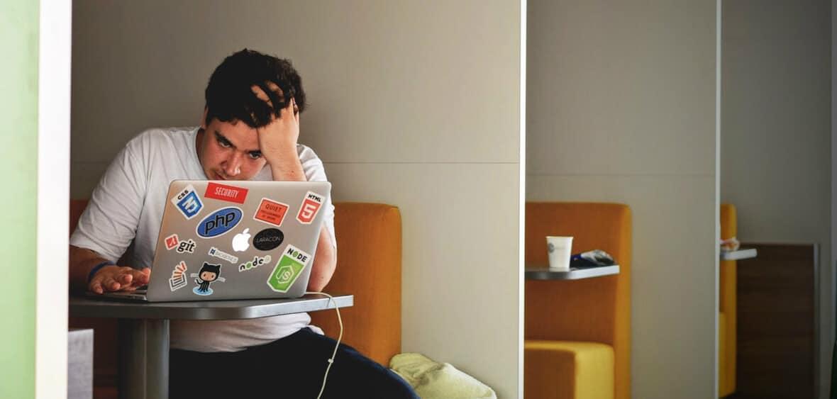 jovem em frente ao seu computador, decorado com muitos autocolantes divertidos, está com a mão na cabeça e com um ar muito preocupado