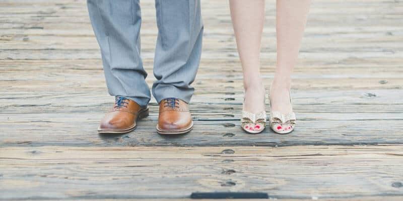 pés de um homem e pés de uma mulher com sandálias lado a lado