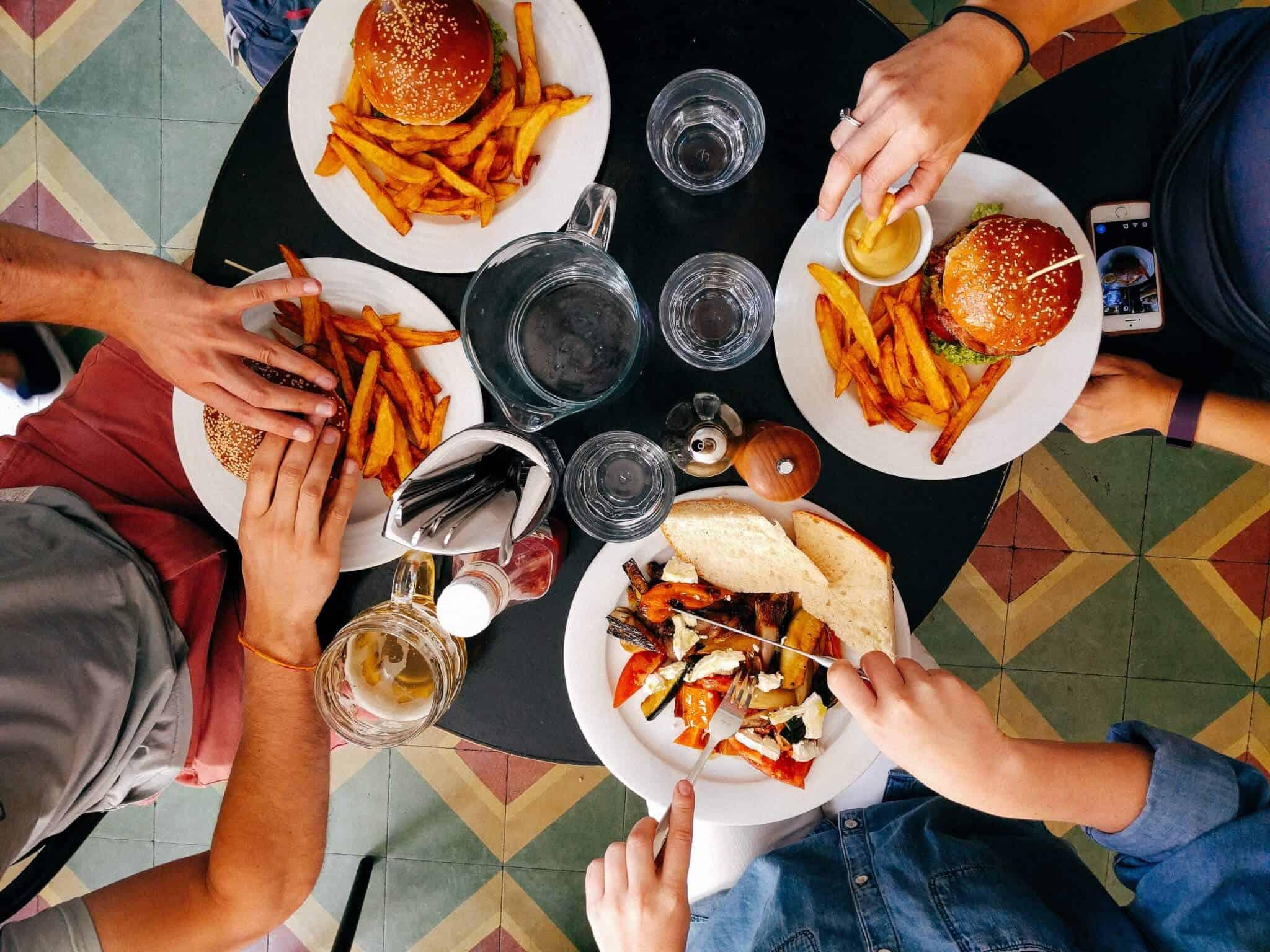 amigos reunidos à mesa com comida e bebida