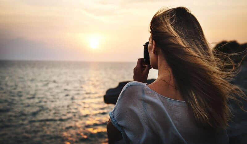 rapariga a tirar foto a beira mar