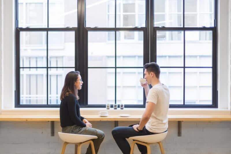 duas pessoas a falar e a beber café