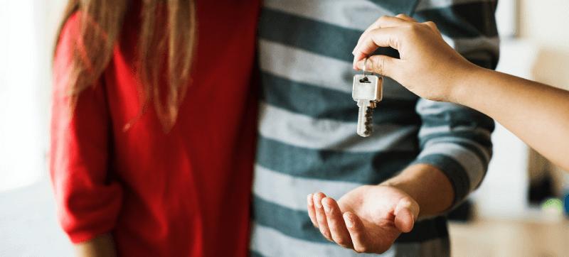 pessoa a entregar chave a casal