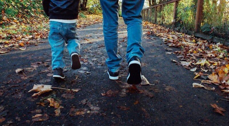 pai e filho a andar numa rua no outuno