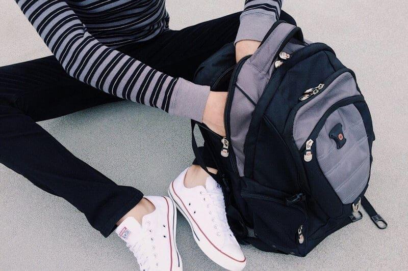regresso Às aulas rapariga a mexer na mochila