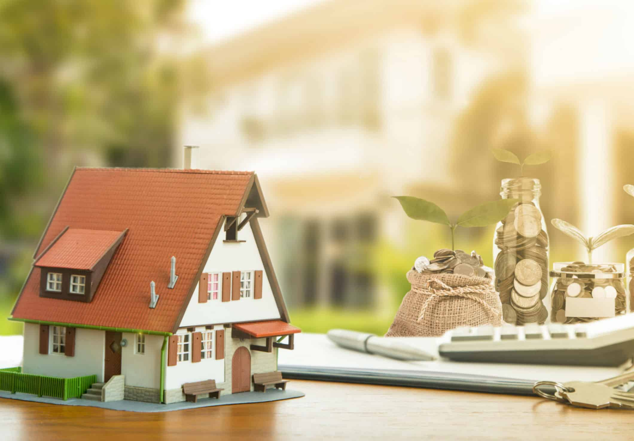 imagem de uma casa em miniatura e sacos com moedas ao lado