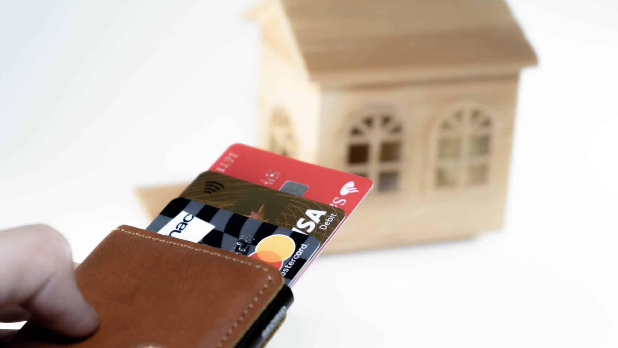 carteira com vários cartões e uma casa de madeira ao longe