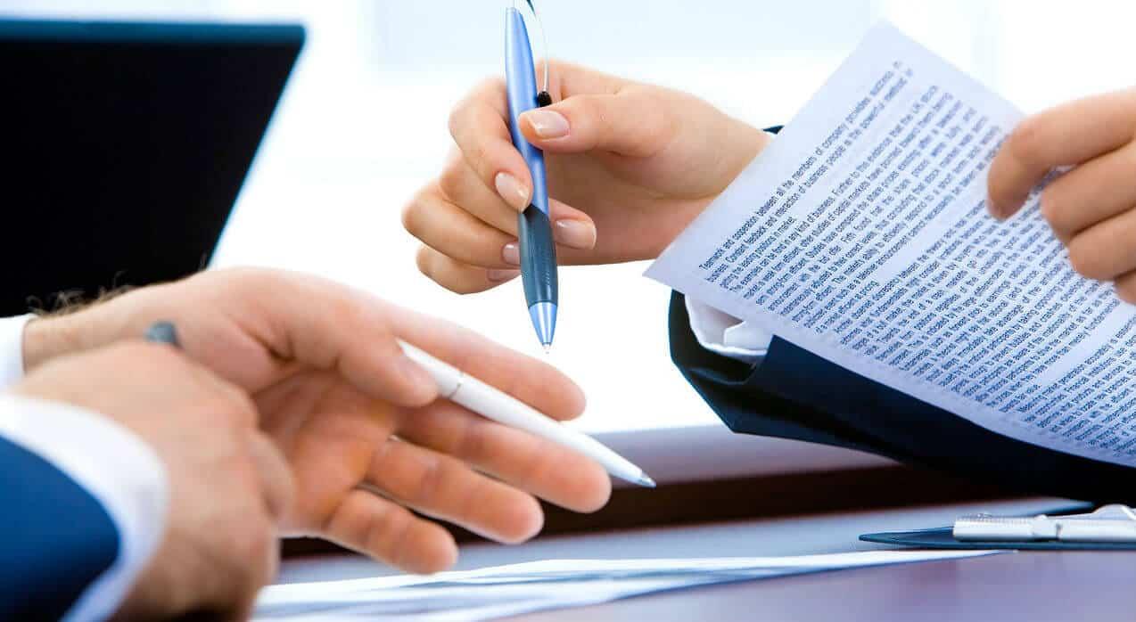 duas pessoas a rever documentos de papel com canetas