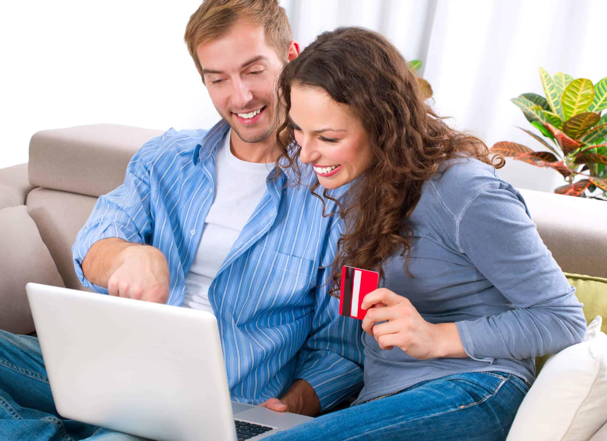 casal a olhar para o computador enquanto estão sentados no sofá