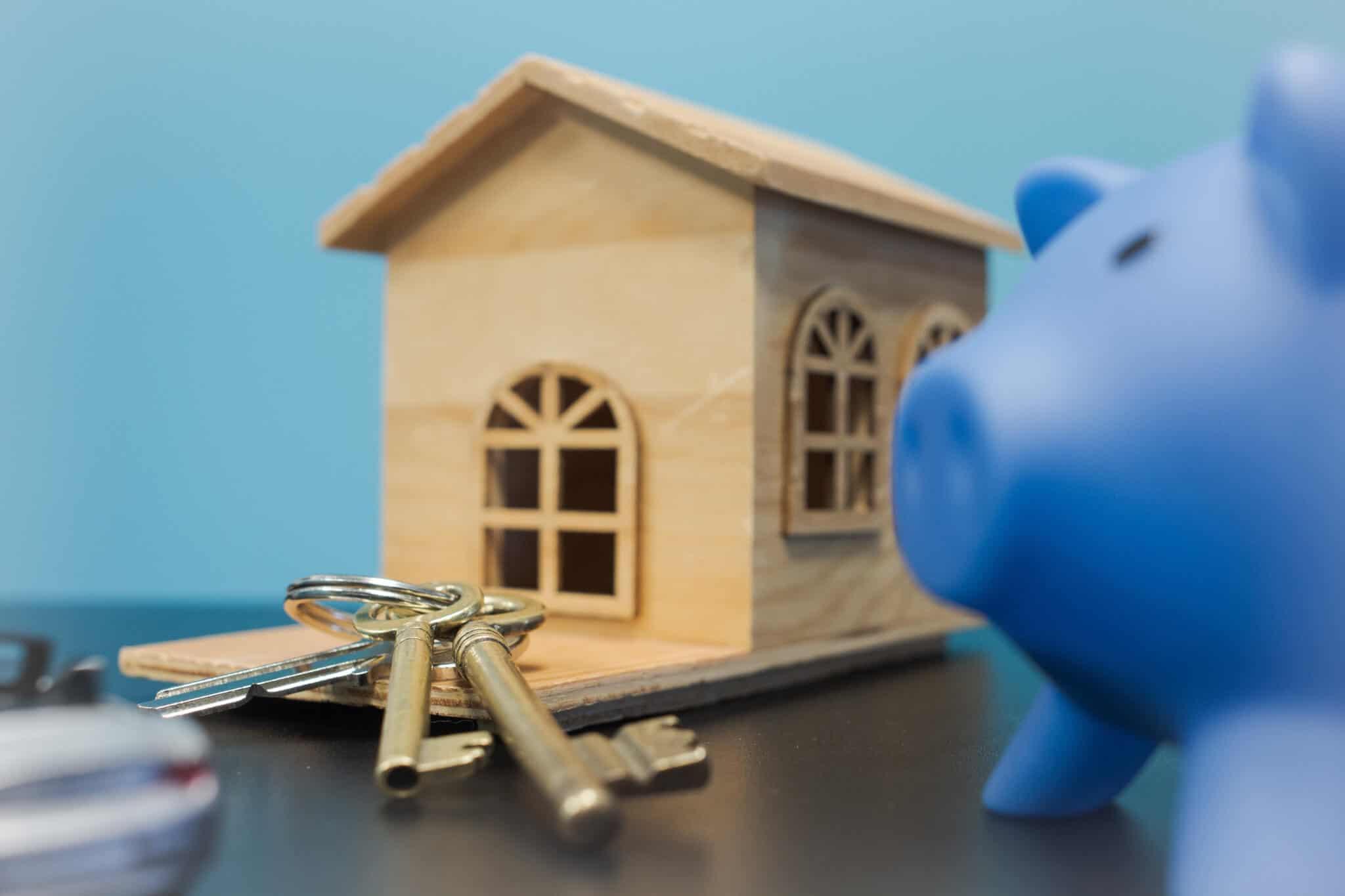 casa de madeira com chaves e um porco mealheiro azul perto