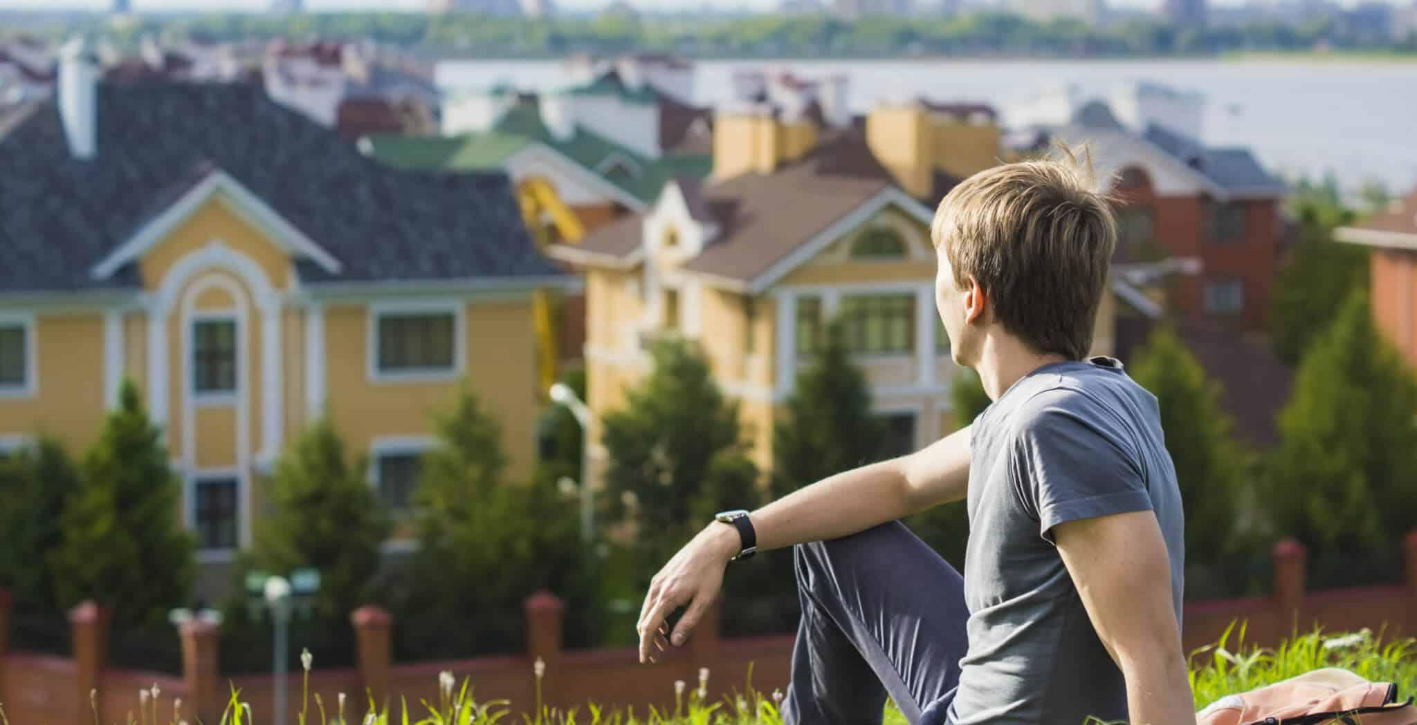 homem sentado a olhar para casas