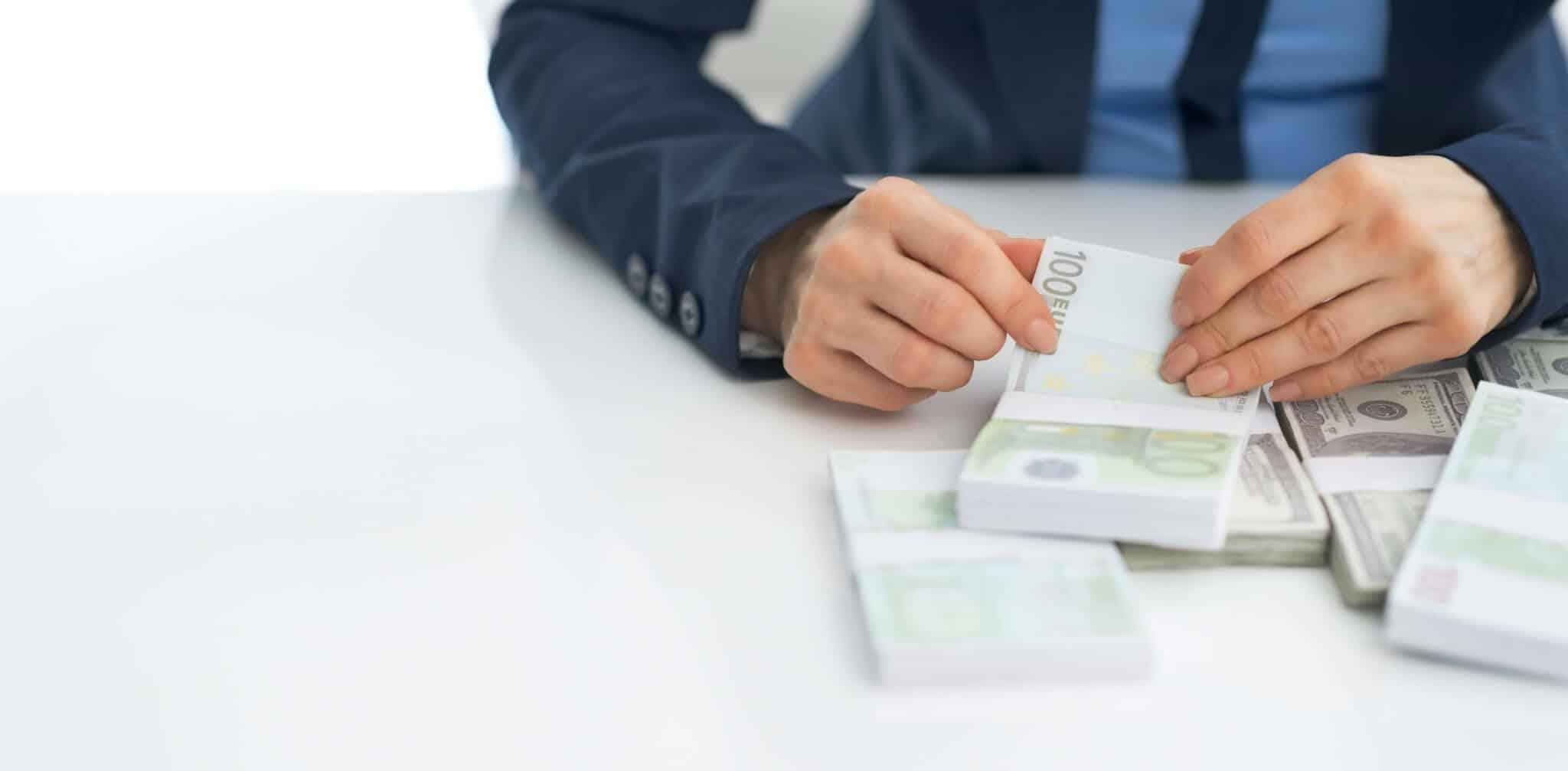 homem a mexer em notas de 100 euros