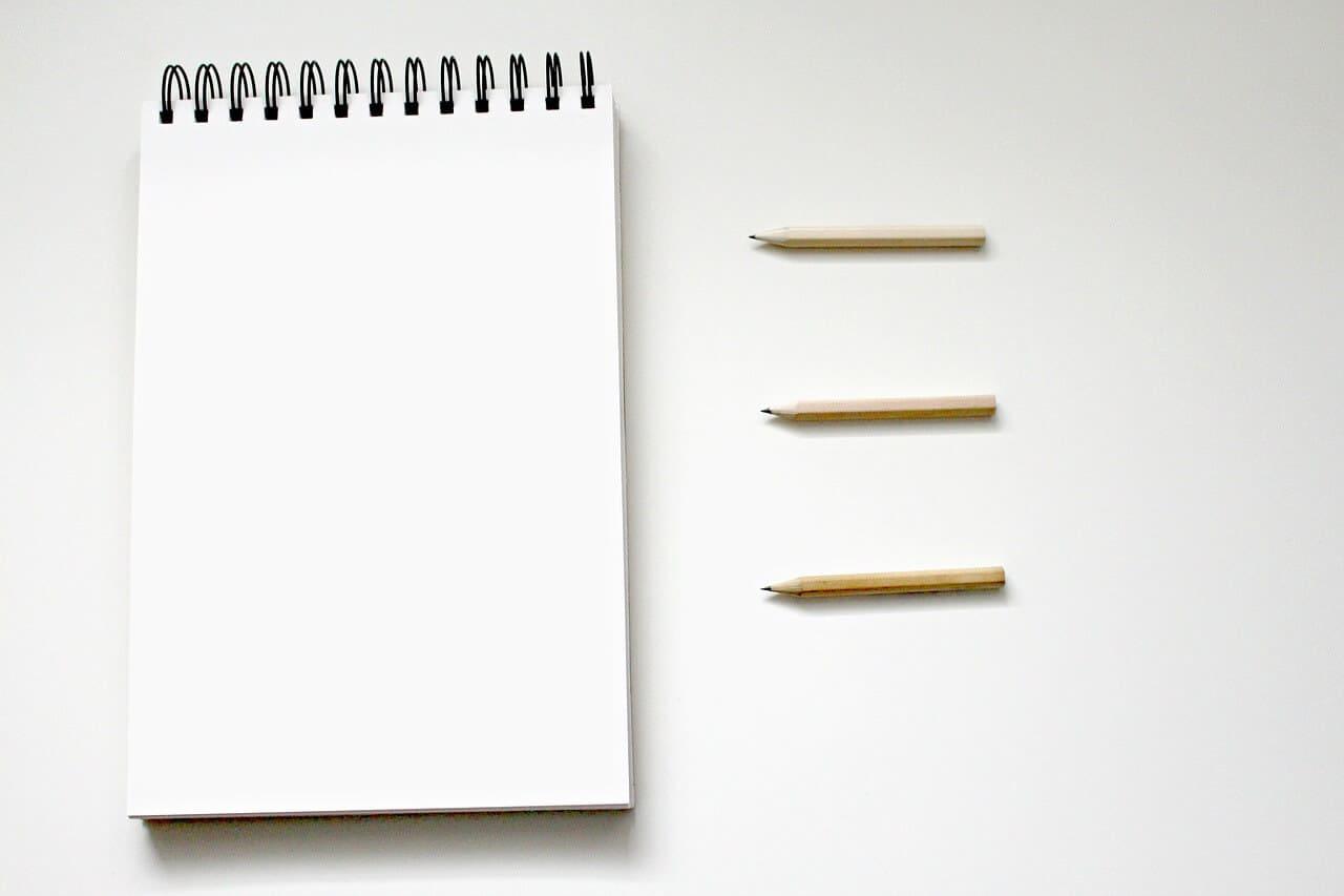 bloco de notas vazio com três lápis do lado direito