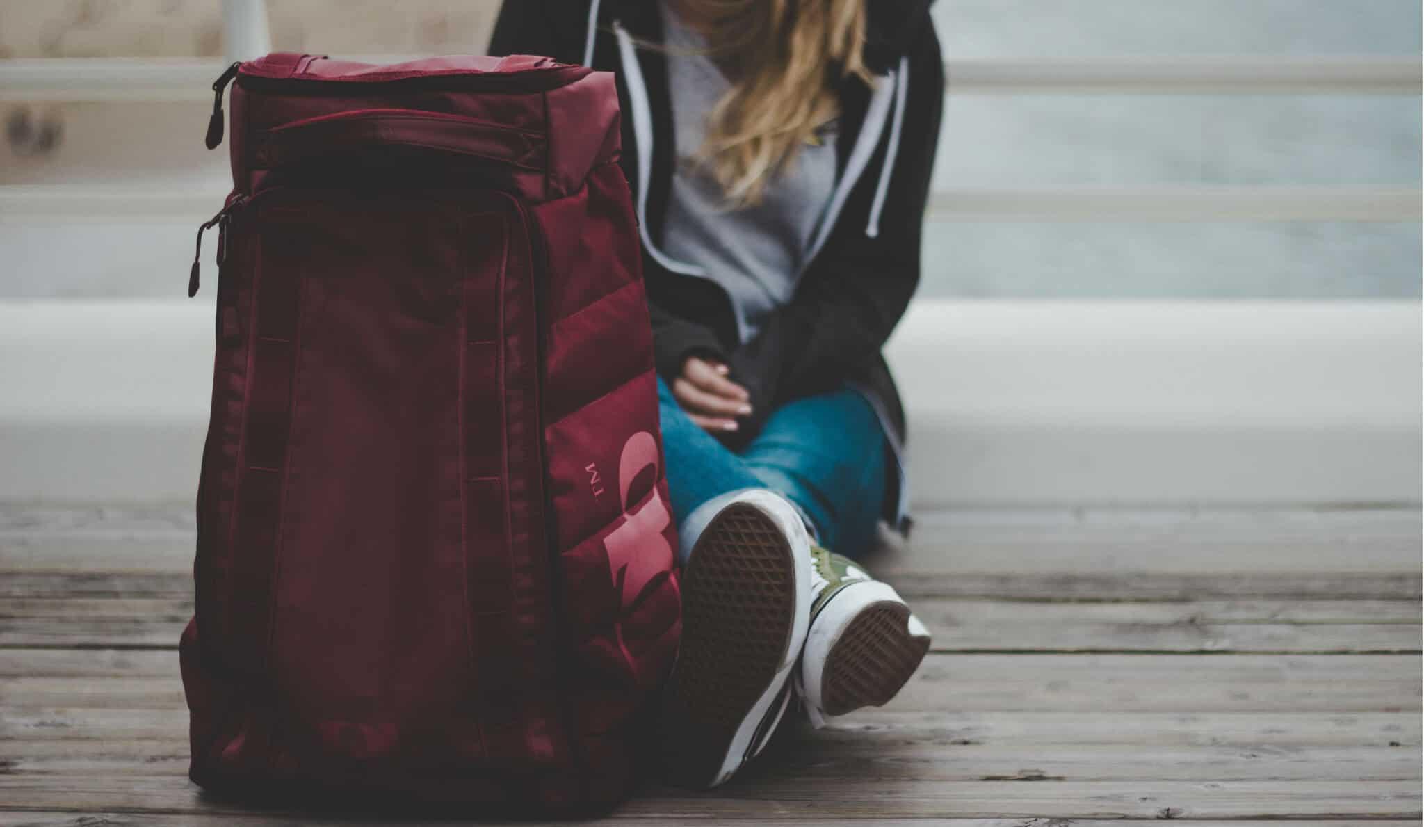 rapariga estudante com uma mochila de viagem vermelha
