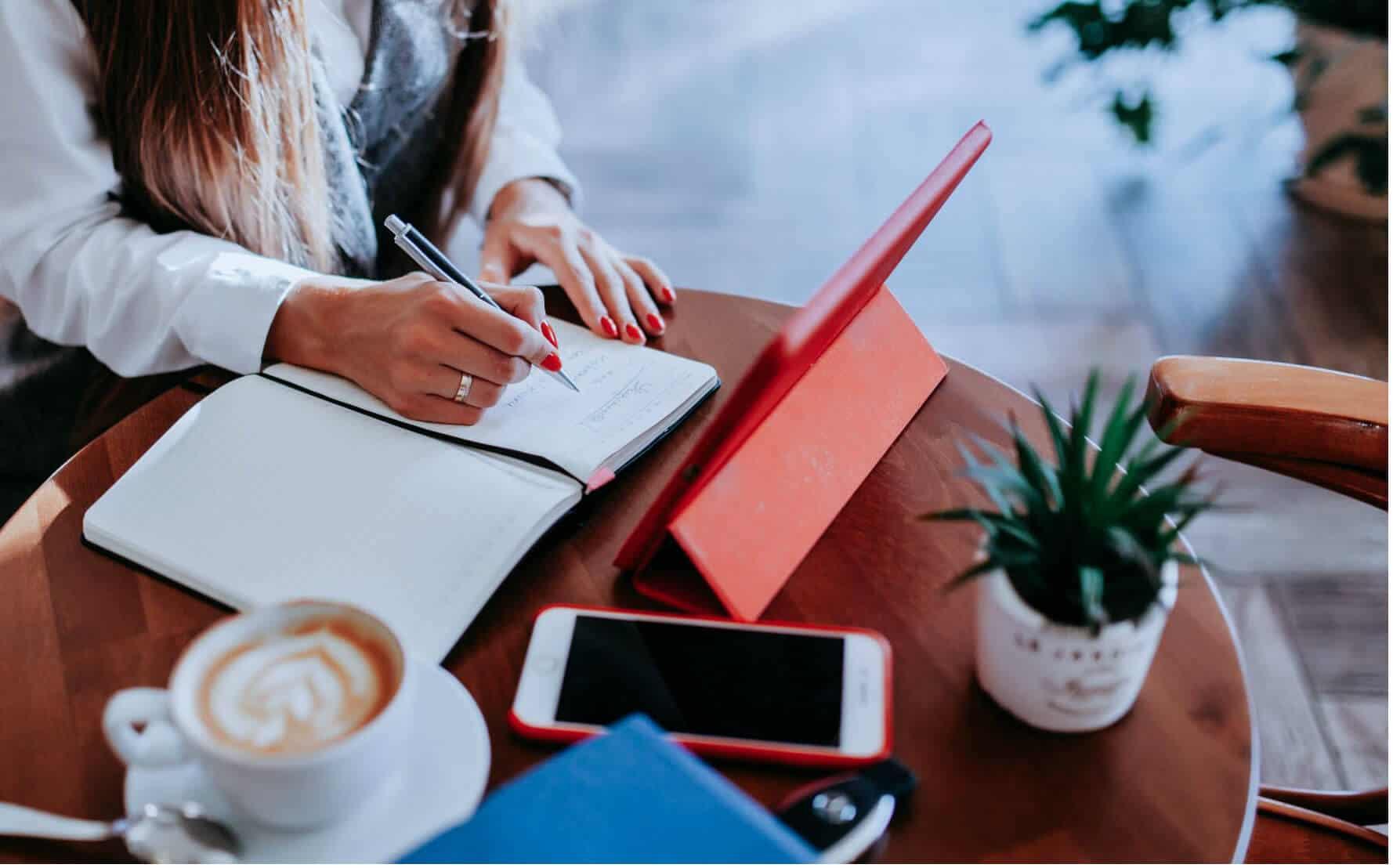 mulher a trabalhar com bloco de notas e tablet vermelho