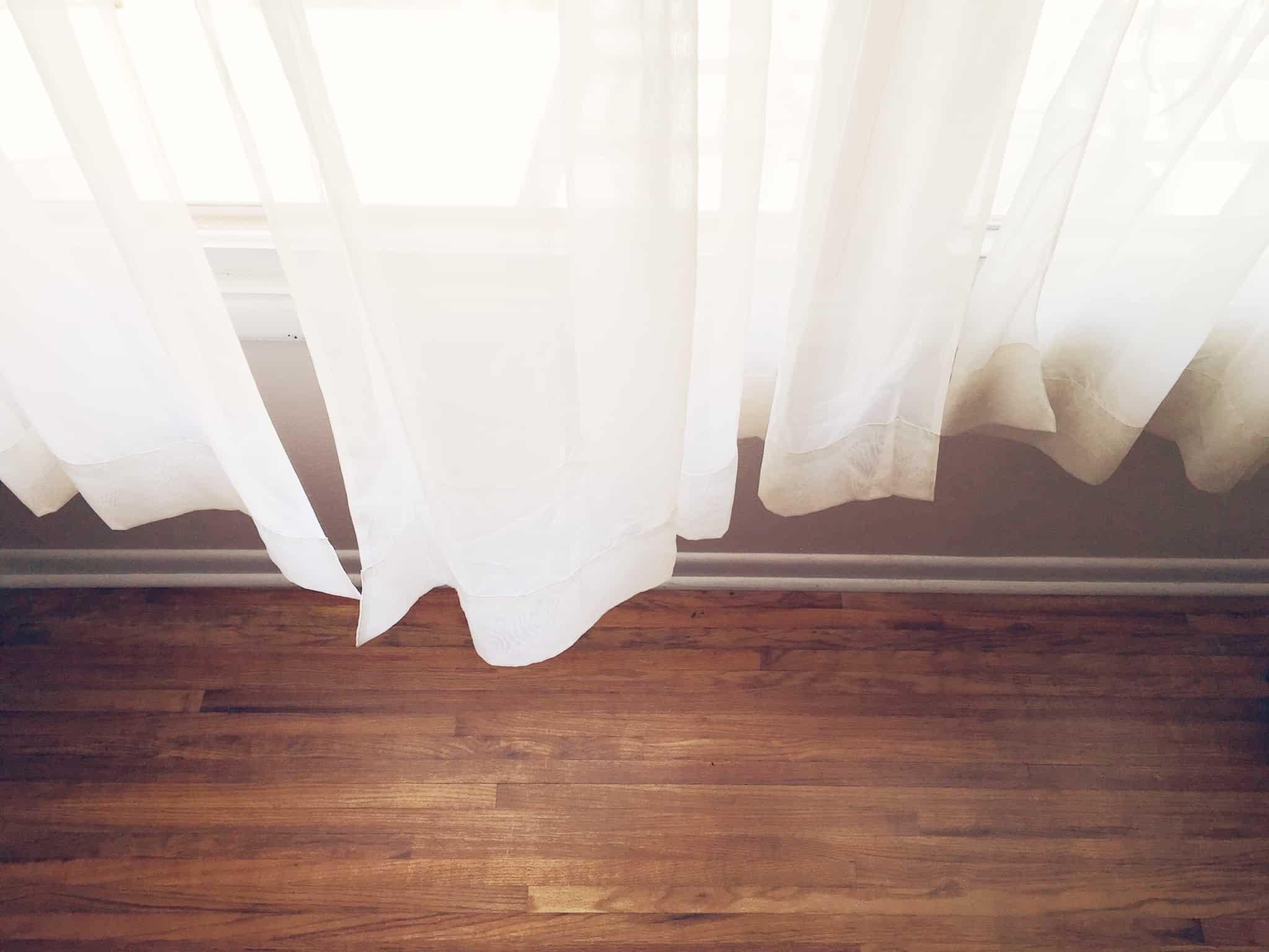 cortinas bancas de uma janela e um chao de madeira