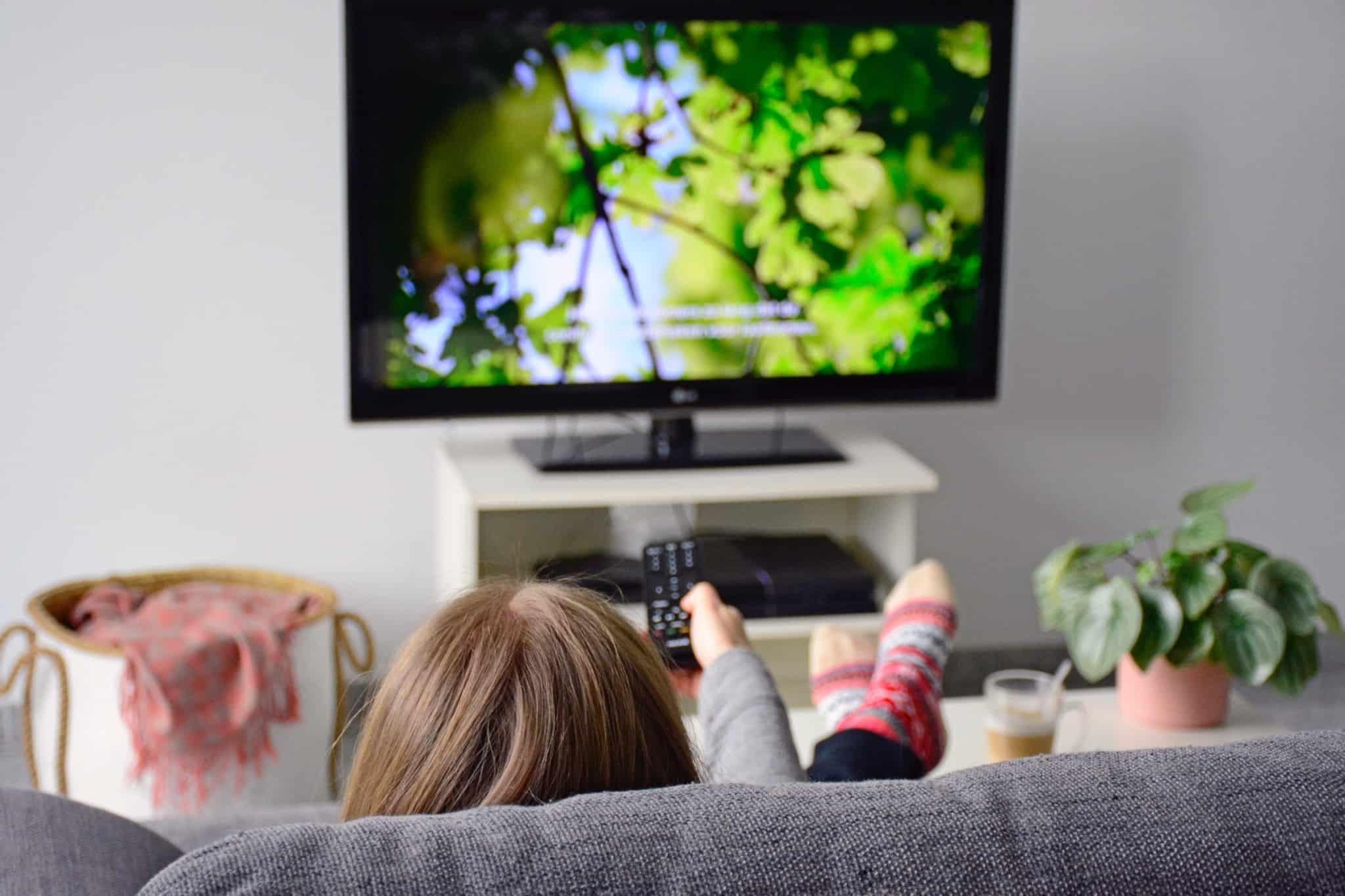 jovem rapariga no sofá com o comando na mão a ver televisão