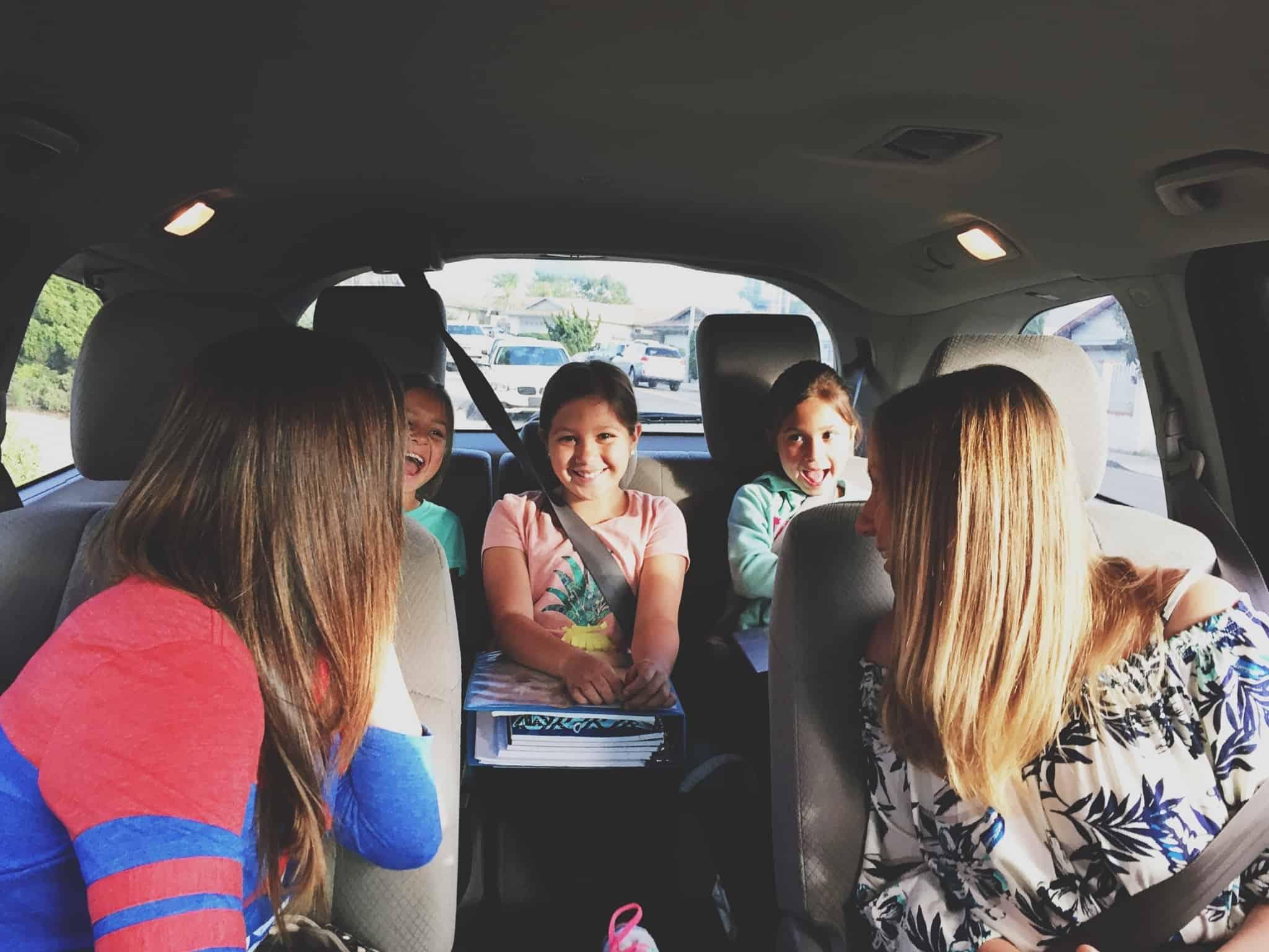 carro familiar com duas mulheres a frente e três crianças