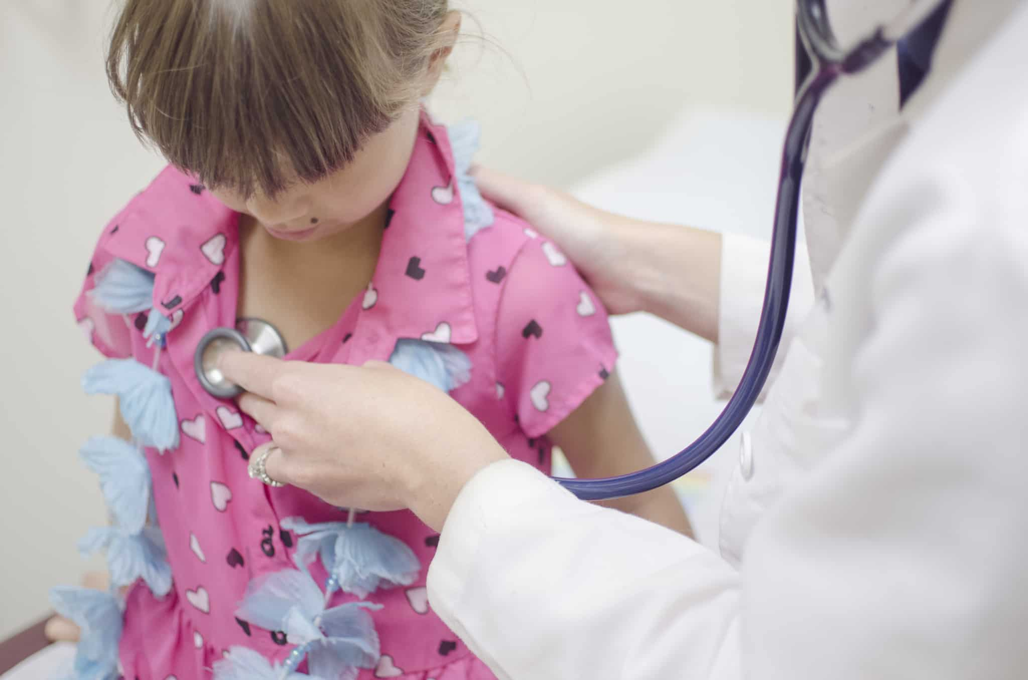 médica a fazer check up a criança com tshirt cor de rosa