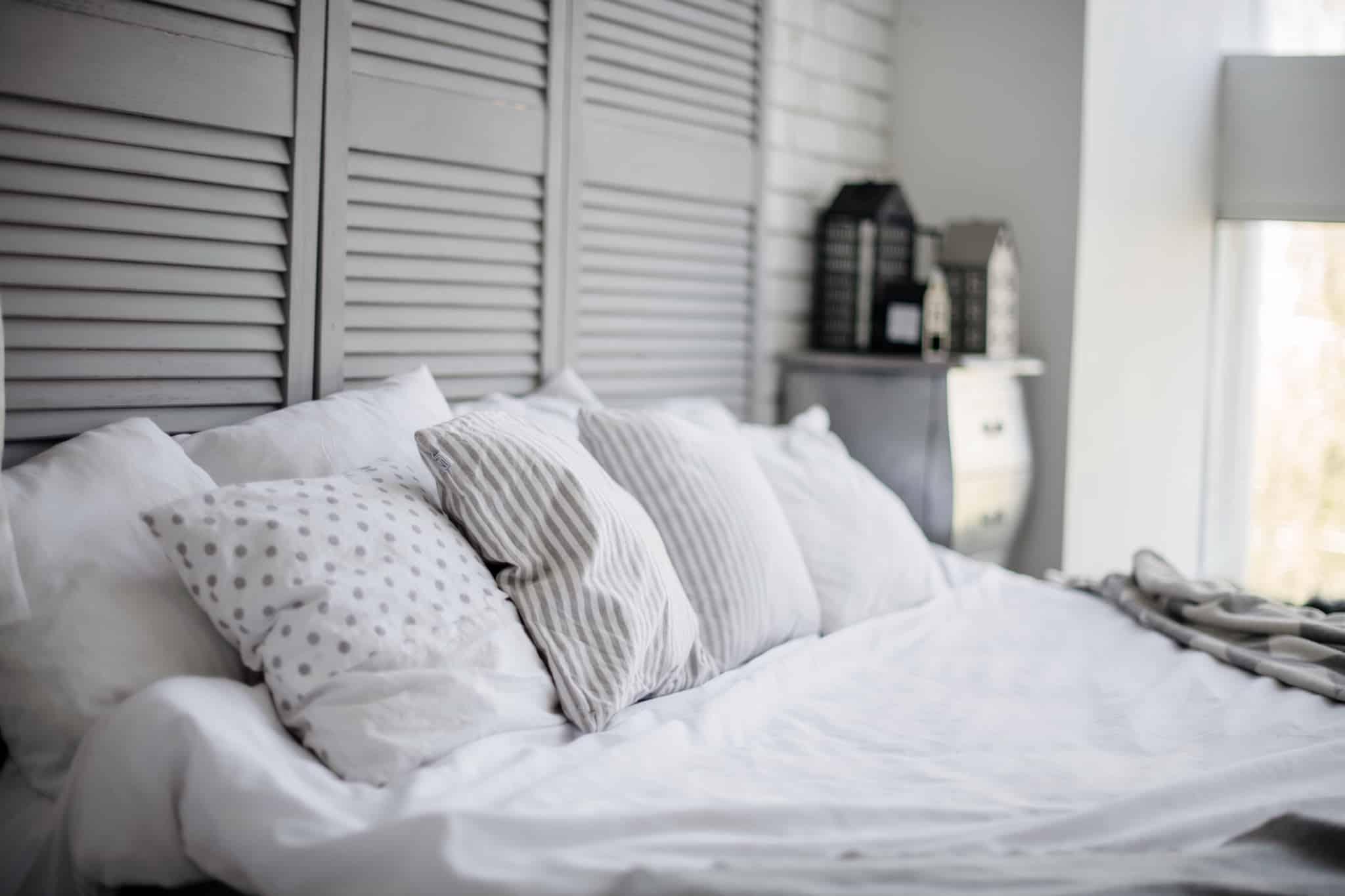 quarto com cama grande e quatro almofadas brancas