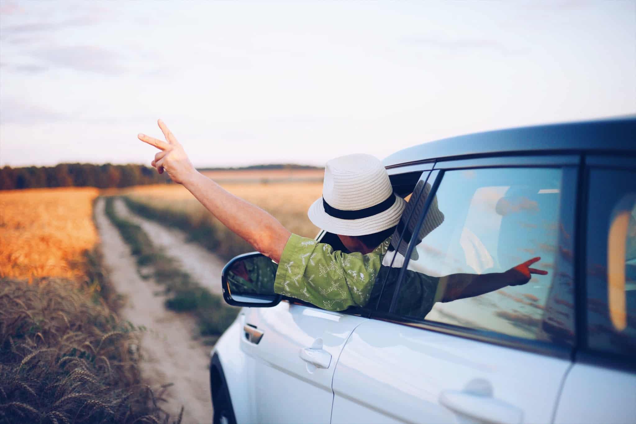 homem aventureiro dentro de um carro branco com o braço de fora