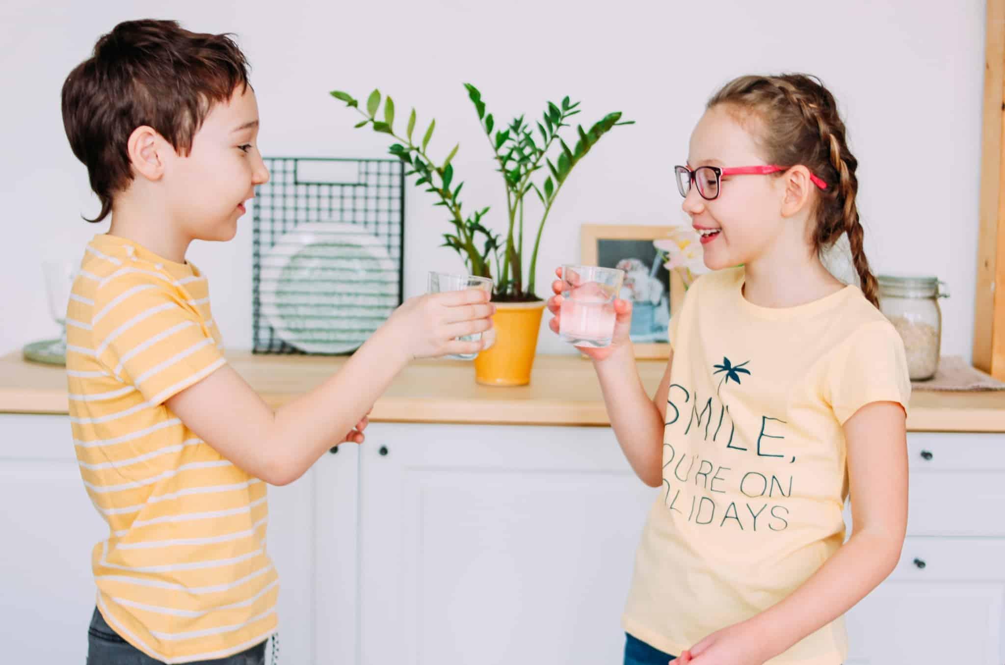 crianças a beber copos de água