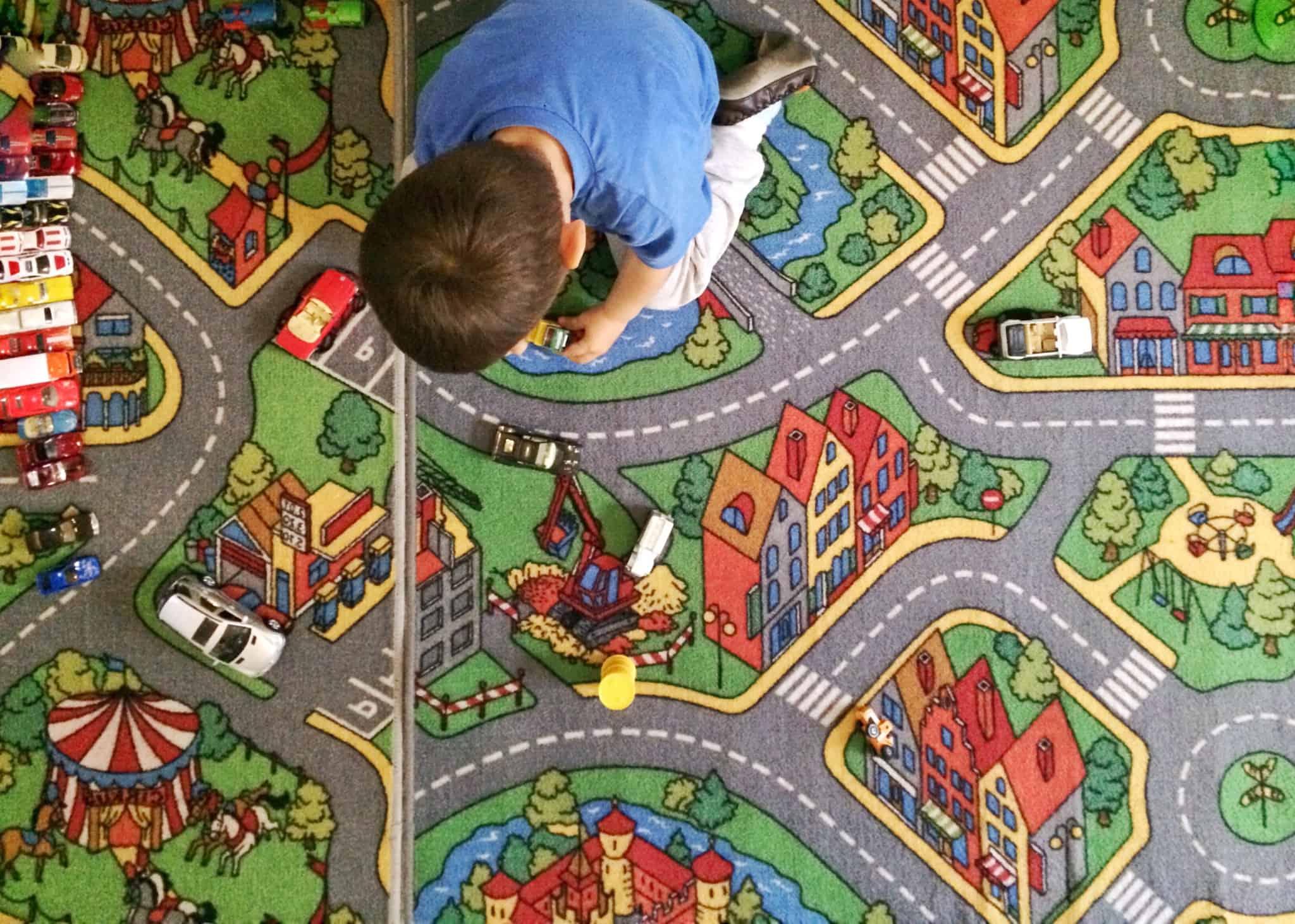 criança a brincar num tapete de uma cidade