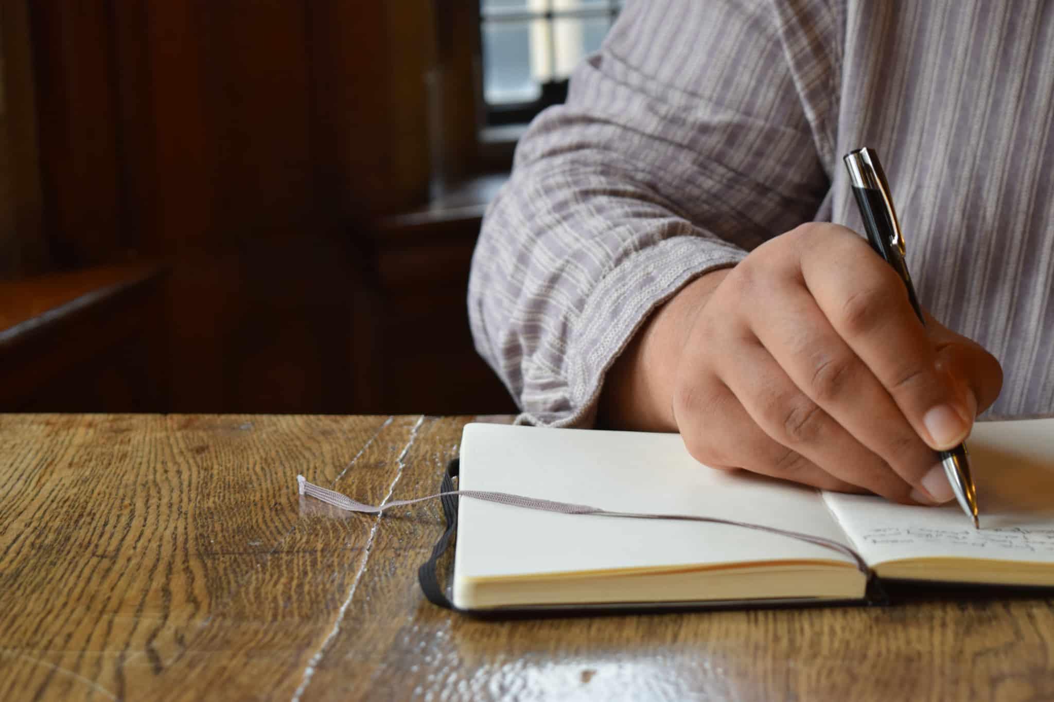 pessoa a escrever com uma caneta preta
