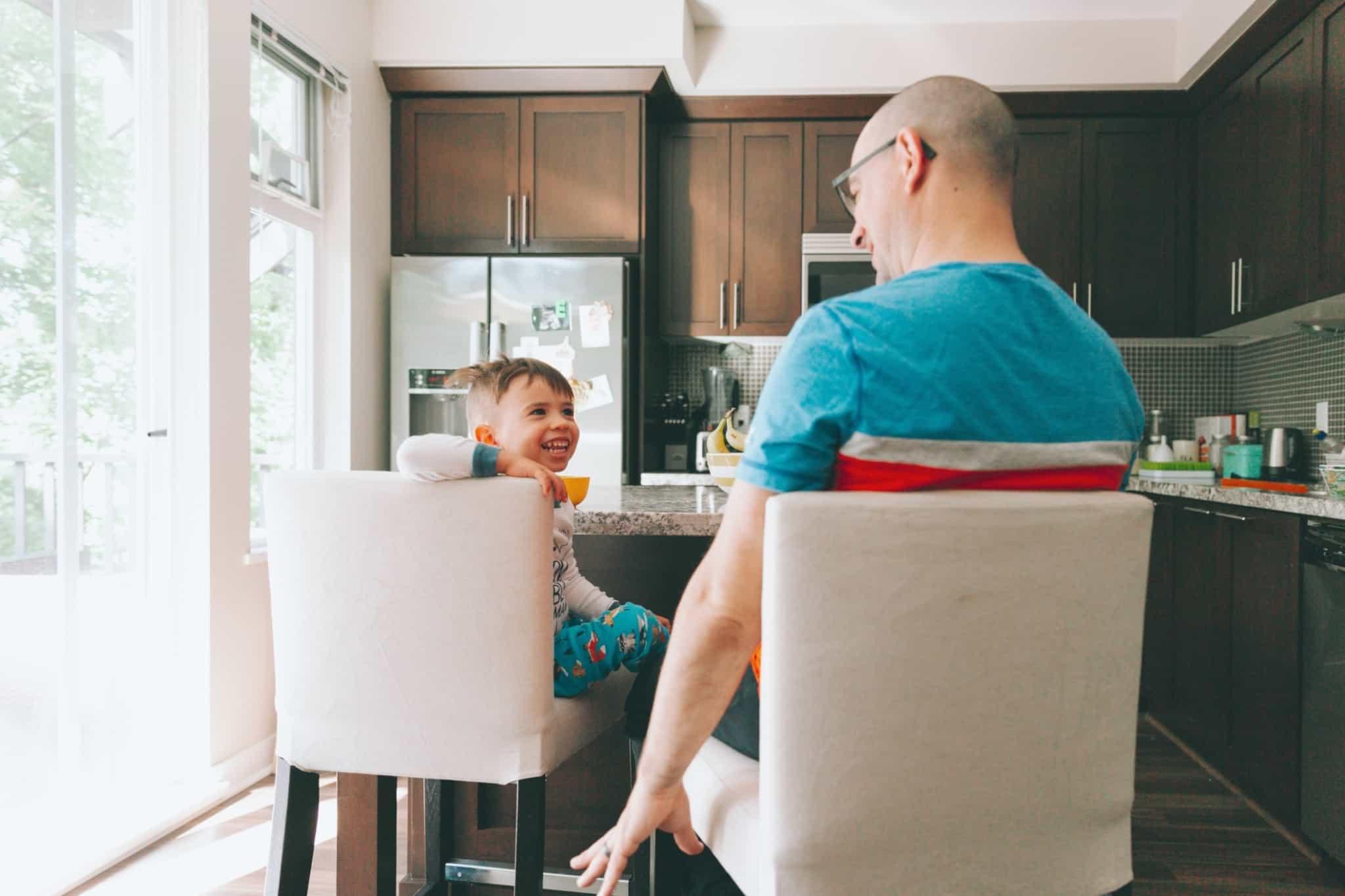 Criança a brincar com o pai, sentado à mesa