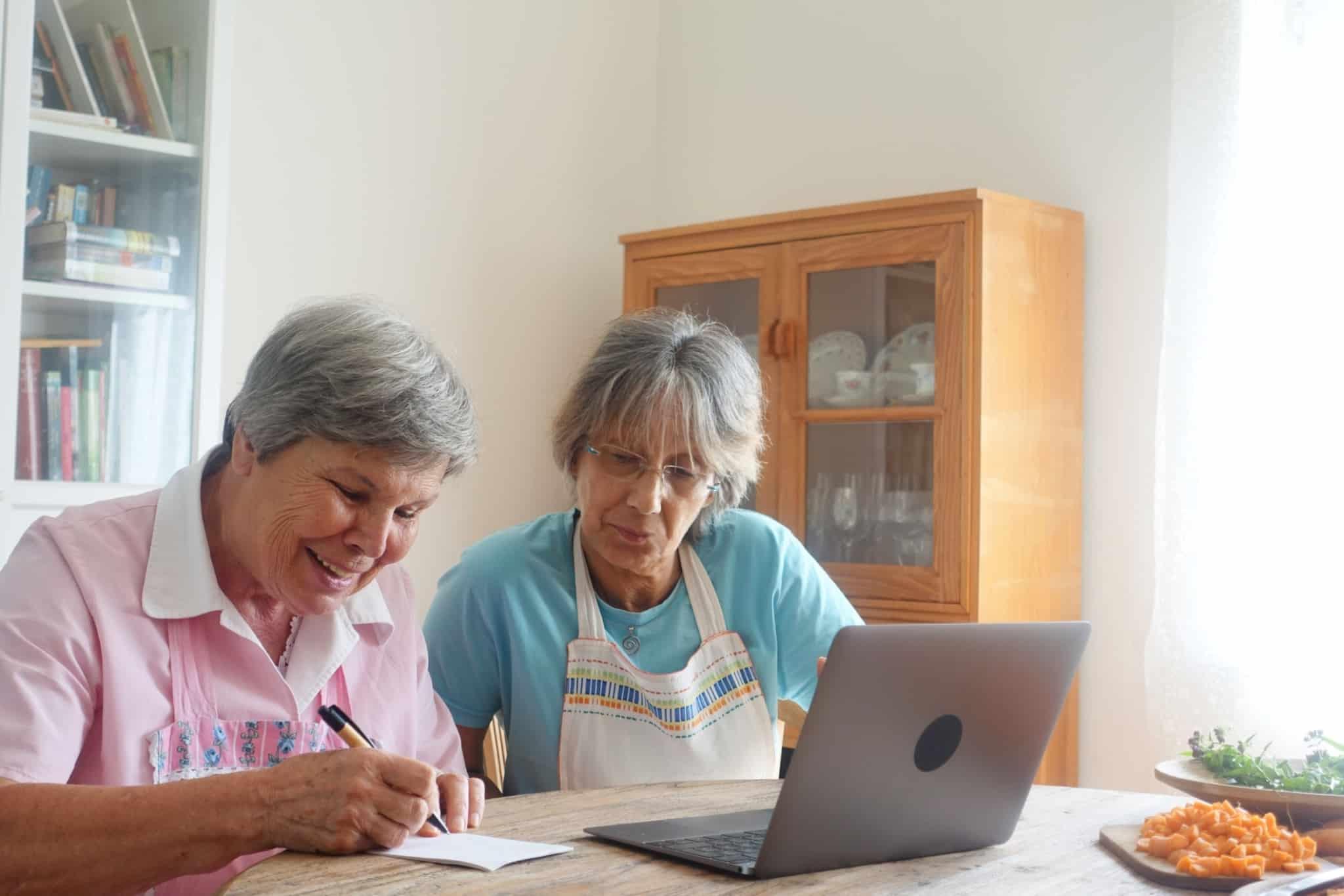 duas irmãs idosas a escrever num papel