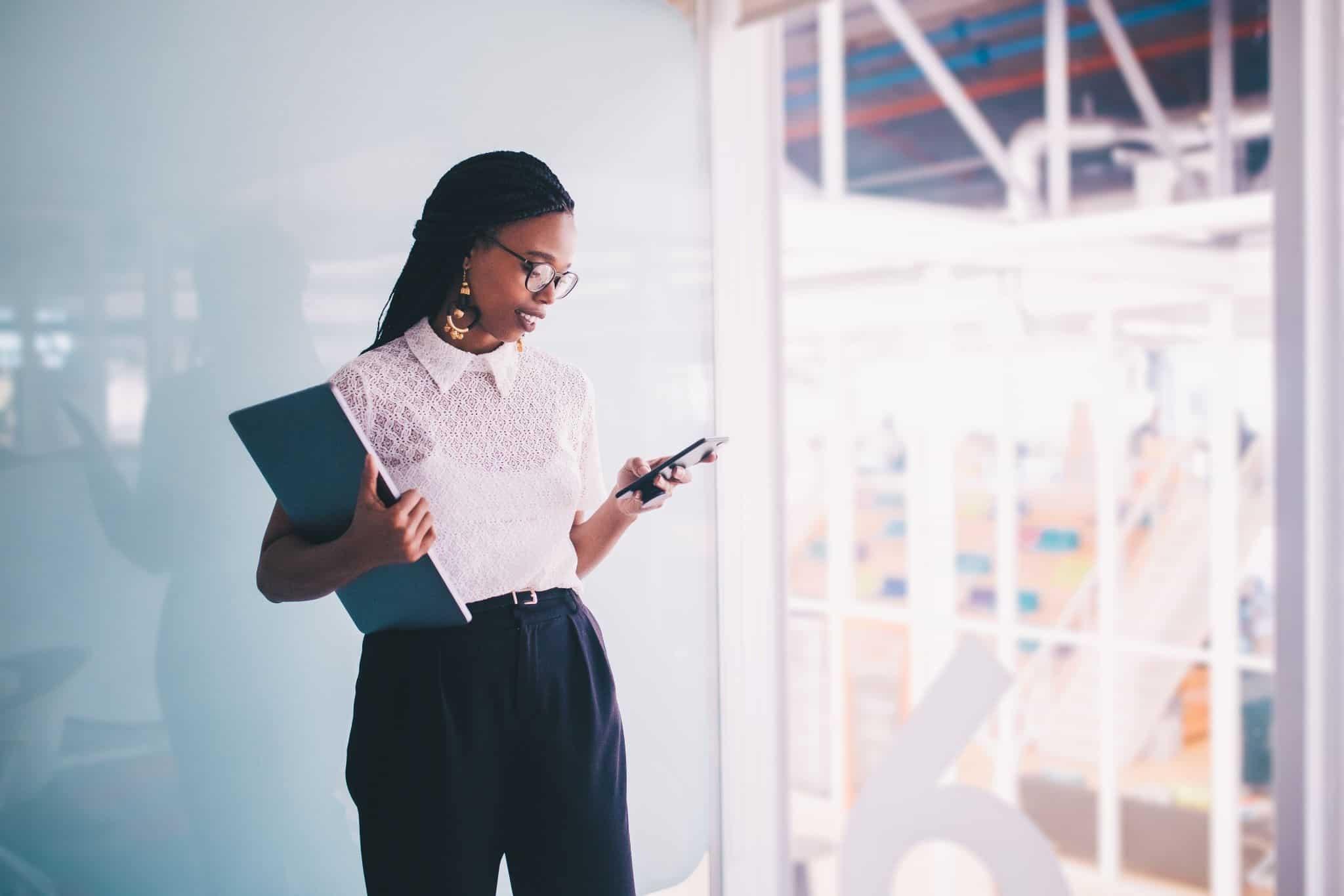 jovem mulher num escritório a segurar um telemóvel e uma pasta de documentos